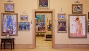 Photo of a gallery wall with paintings hanging.