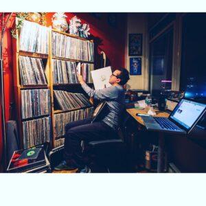 DJ near a large book case of vinyls.