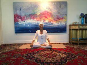 A woman sitting cross legged on a yoga rug.